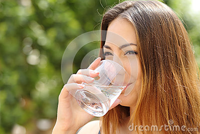 happy-woman-drinking-water-glass-outdoor-healthy-fresh-green-background-42150243